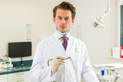 Dentist in his surgery, he holds a drill Stock Photo
