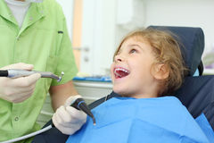 Dentist hold grinding drill, girl opens her mouth. Dentist hands hold saliva suction and grinding drill, happy girl opens her mouth in dental clinic Stock Image