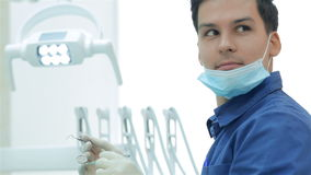 Dentist holding a dental instrument in his hands stock video footage