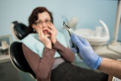 Dentist holding dental tool - remover. On the background woman frightened by dentists and covering her mouth with hands Stock Image