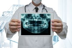 Dentist holding a digital tablet with x-ray of teeth in dental office stock photos