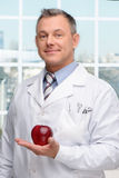 Dentist holding red apple Stock Image