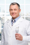 Dentist holding stomatologist tools. Photo of dentist holding stomatologist tools and looking at camera. Concept for teeth hygiene royalty free stock photography