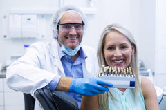 Dentist holding teeth shades while female patient smiling Stock Photography