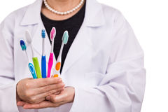 Dentist holding toothbrushes with different head and bristle design. For various oral needs stock photo