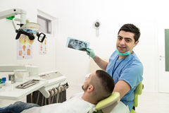 Dentist Holding X-Ray And Examse White Patient Stock Image