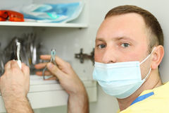 Dentist holds dental instruments and looks. Dentist in mask holds metal dental instruments and looks at camera Stock Images