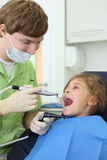 Dentist holds grinding drill, girl opens mouth. Young dentist holds saliva suction and grinding drill, happy girl opens her mouth in dental clinic Royalty Free Stock Photography