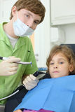 Dentist holds grinding drill and patient girl Royalty Free Stock Images