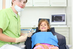 Dentist holds instruments and girl lies in chair Royalty Free Stock Photo