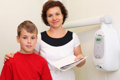 Dentist holds jaw x-ray image and hugs boy Royalty Free Stock Photo