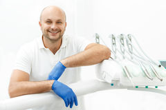 Dentist leaning on the tray of dental instruments. Handsome dentist is leaning on the tray of dental instruments Stock Images