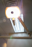 Dentist lighting equipment powered on from the angle of the patient's seat. Stock Photography