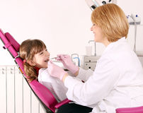 Dentist and little girl dental exam Stock Photos