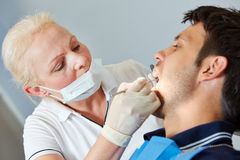 Dentist looking for caries in mouth of patient Stock Image