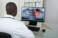 Dentist Looking At Teeth X-ray On Computer Stock Image