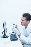 Dentist looking at x-ray by computer Stock Image