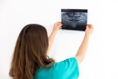 Dentist looking at x-ray Royalty Free Stock Photos