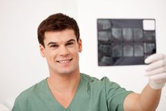 Dentist Looking at X-rays Royalty Free Stock Image