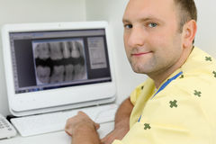 Dentist looks at camera and sits with teeth X-rays Royalty Free Stock Photos