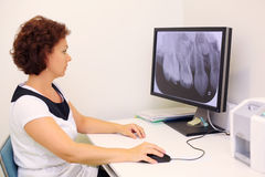 Dentist looks at jaw x-ray image on monitor Stock Photography