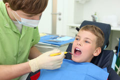 Dentist looks at teeth of boy in dental clinic Stock Photo