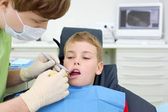 Dentist looks at teeth of boy in dental clinic Royalty Free Stock Photo