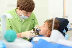 Dentist looks at teeth of girl Royalty Free Stock Image