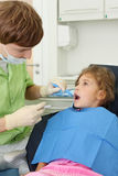 Dentist looks at teeth of girl in dental clinic Stock Images