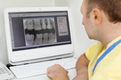 Dentist looks at teeth X-rays at computer monitor Stock Photos