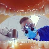 Dentist with loops drilling teeth Stock Photos