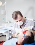 Dentist makes dental treatment to patient. Stock Photos