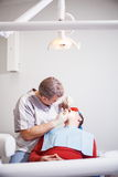 Dentist makes teeth treatment. Royalty Free Stock Images