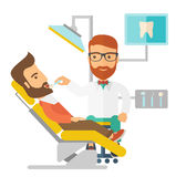 Dentist man examines a patient teeth in the clinic Stock Images