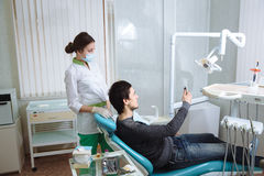 Dentist man with his patient doing photo selfie in dental office. Concept of healthy Royalty Free Stock Photo