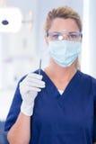 Dentist in mask holding dental explorer Stock Photography