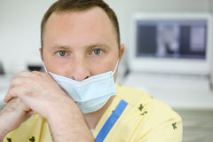 Dentist in mask looks at camera in dental clinic Stock Photo