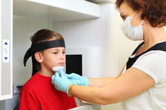 Dentist in mask prepares boy to jaw x-ray image Royalty Free Stock Photos