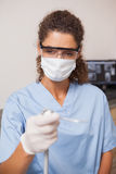 Dentist in mask and protective glasses holding drill Stock Photography
