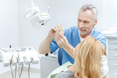 Dentist matching teeth colour with palette royalty free stock image