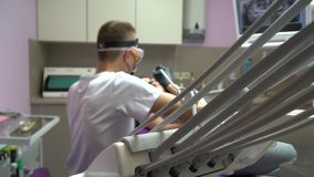 Dentist in medical mask is drilling patient`s teeth. A brunette woman patient in dental office: room with purple dental. Doctor is drilling women`s teeth in stock video footage
