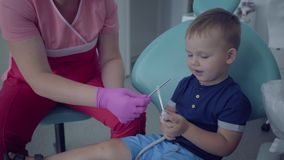 Dentist in medical mask and gloves ready to checking tooths of little carefree boy sitting in the chair in the dental. Office. Female professional doctor stock footage