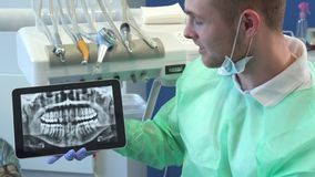 Dentist moves the x-ray image on his tablet. Attractive caucasian dentist in medical uniform moving x-ray image on his tablet. Close up of young blond dental Royalty Free Stock Photos
