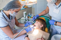 Dentist and nurse curing childe teeth Stock Photo