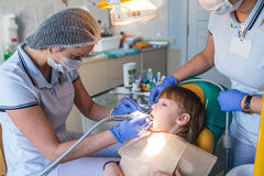 Dentist and nurse curing childe teeth Royalty Free Stock Images