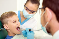 Dentist. And nurse are curing a little boy patient royalty free stock images