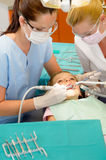 Dentist and nurse curing little girl Stock Photo
