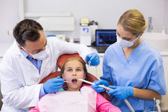 Dentist and nurse examining a young patient with tools. In clinic Stock Photos