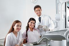 Dentist And Nurse With Patient In Clinic Stock Photo