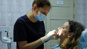 Dentist orthodontist puts a dental fixator for a woman to install a bracket system. Visit to the dentist. Dentist orthodontist puts a dental fixator for a women stock photo